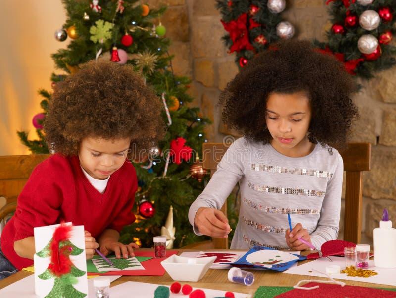 Enfants de chemin mélangé effectuant des cartes de Noël photos libres de droits