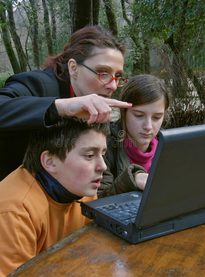 Enfants de enseignement d'une femme à l'ordinateur portatif photos libres de droits