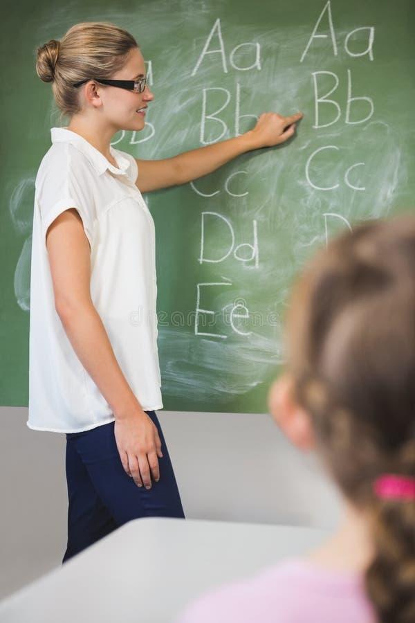 Enfants de enseignement de sourire de professeur sur le tableau dans la salle de classe photo libre de droits