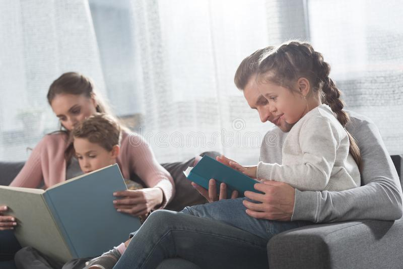 Enfants de enseignement de mère et de père à lire photos stock