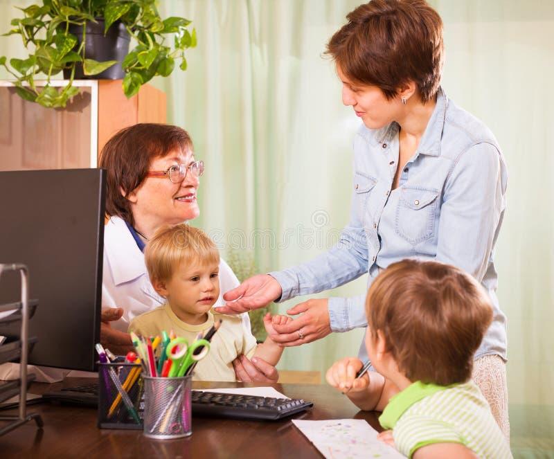 Enfants de examen de docteur amical de pédiatre image stock