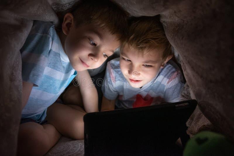 Enfants de frères avec la tablette sous la couverture photo libre de droits