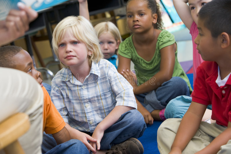 Enfants de jardin d'enfants écoutant une histoire images libres de droits