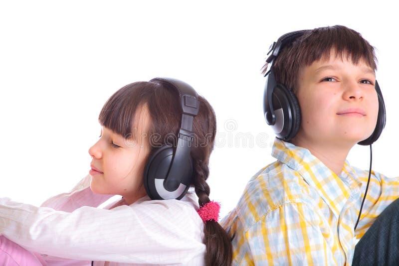 Enfants de mêmes parents écoutant la musique images stock