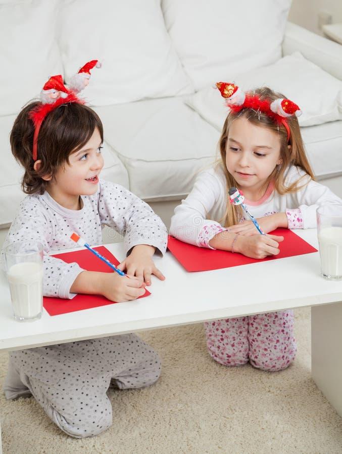 Enfants de mêmes parents écrivant des lettres à Santa Claus photographie stock libre de droits