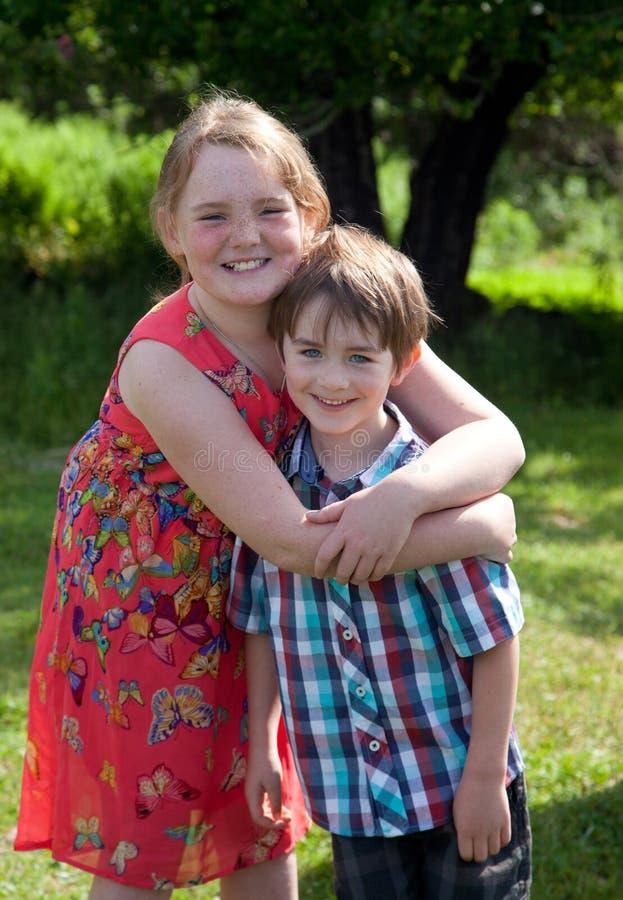 Enfants de mêmes parents étreinte et sourire photo libre de droits