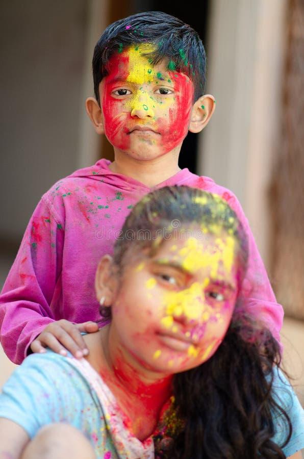 Enfants de mêmes parents adorables mignons jouant avec des couleurs pendant le festival de holi du portrait créatif caucasien asi images stock