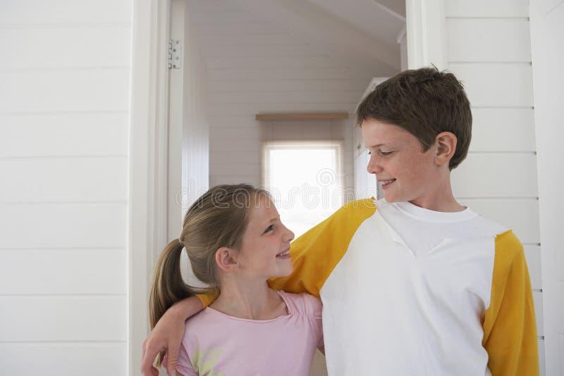 Enfants de mêmes parents avec des bras autour de regarder l'un l'autre image libre de droits