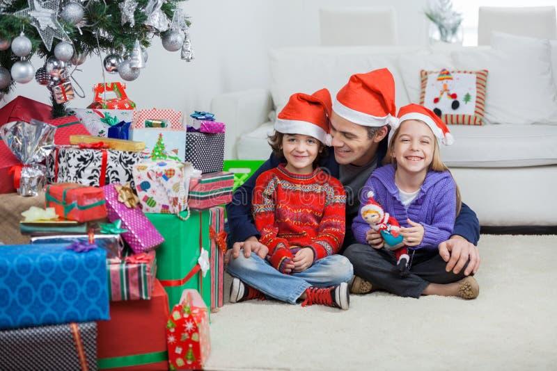 Enfants de mêmes parents avec Noël d'At Home During de père photos stock