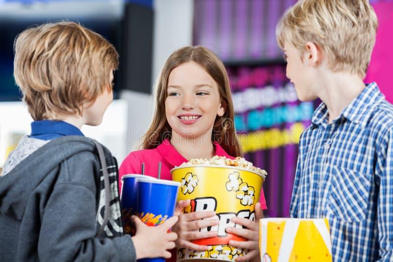 Enfants de mêmes parents conversant tout en tenant des casse-croûte au cinéma photo stock
