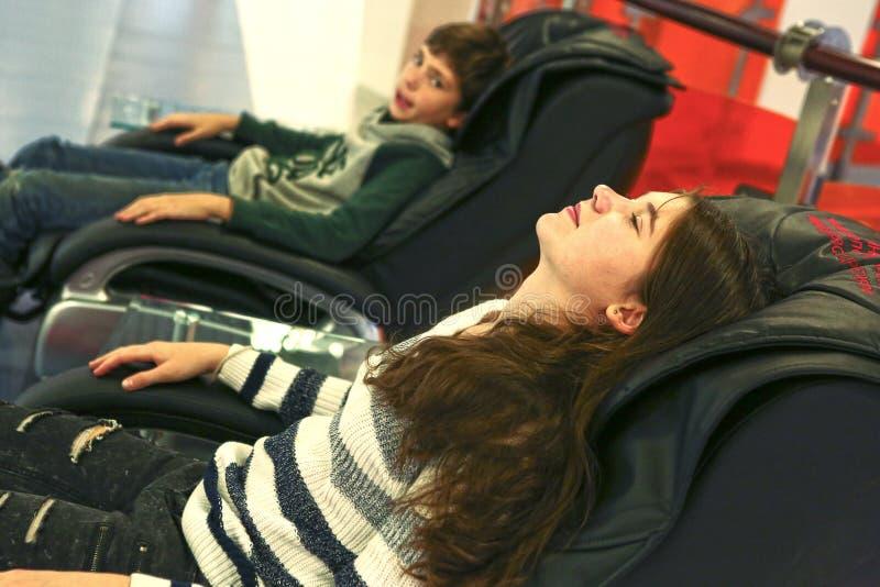 Enfants de mêmes parents de l'adolescence frère et soeur dans la chaise de massage photo stock