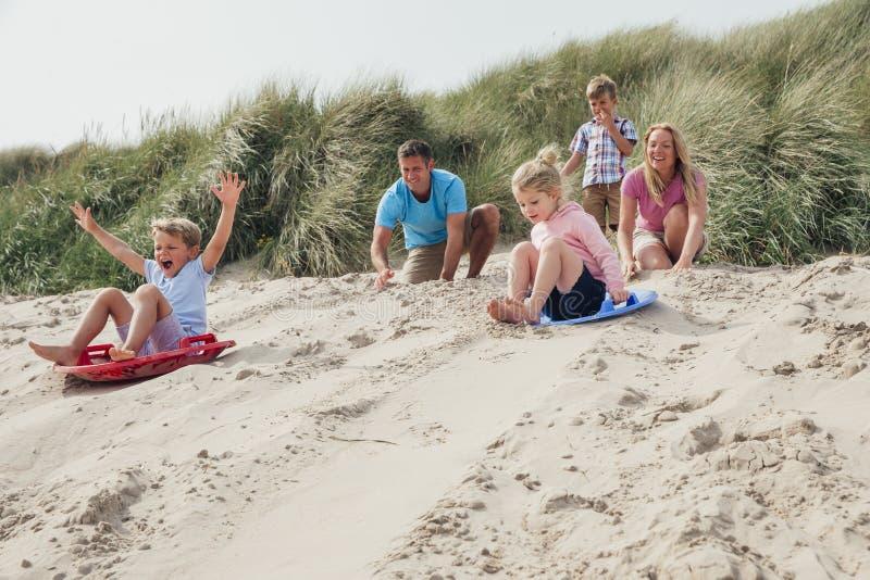 Enfants de mêmes parents emballant en bas des dunes de sable photo stock