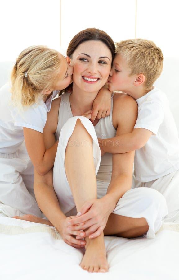 Enfants de mêmes parents embrassant leur mère s'asseyant sur un bâti photographie stock