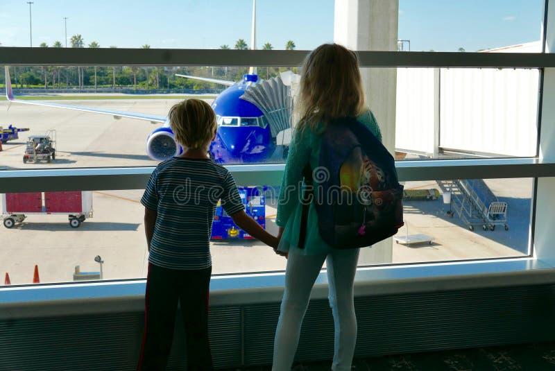 Enfants de mêmes parents ennuyés tout en attendant un vol retardé pour partir photographie stock