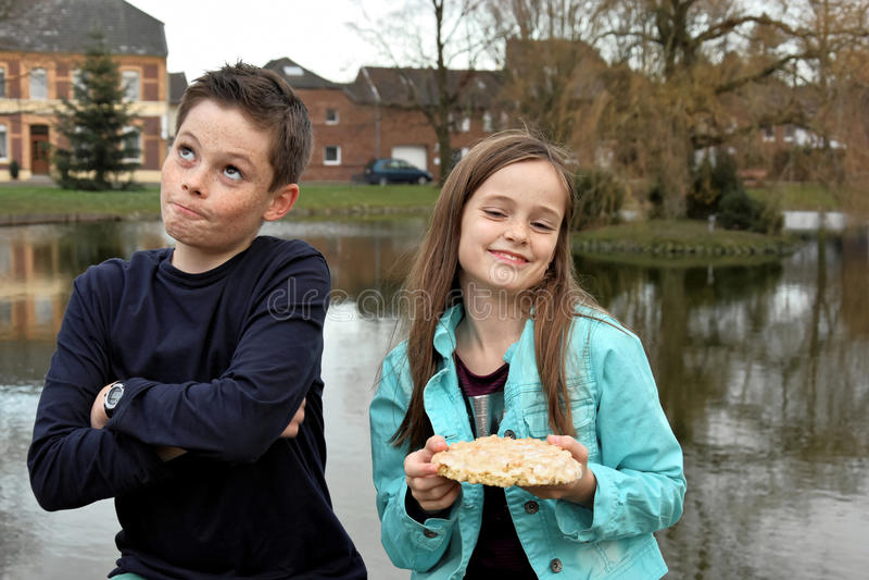 Enfants de mêmes parents et une seule pièce de gâteau images stock