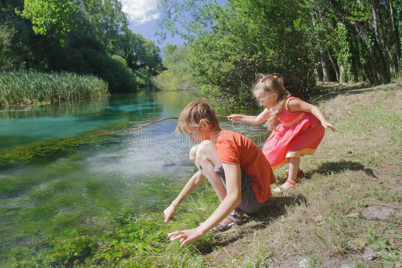 Enfants de mêmes parents de fille et de garçon jouant près de l'eau de la rivière de Tirino d'Italien images libres de droits