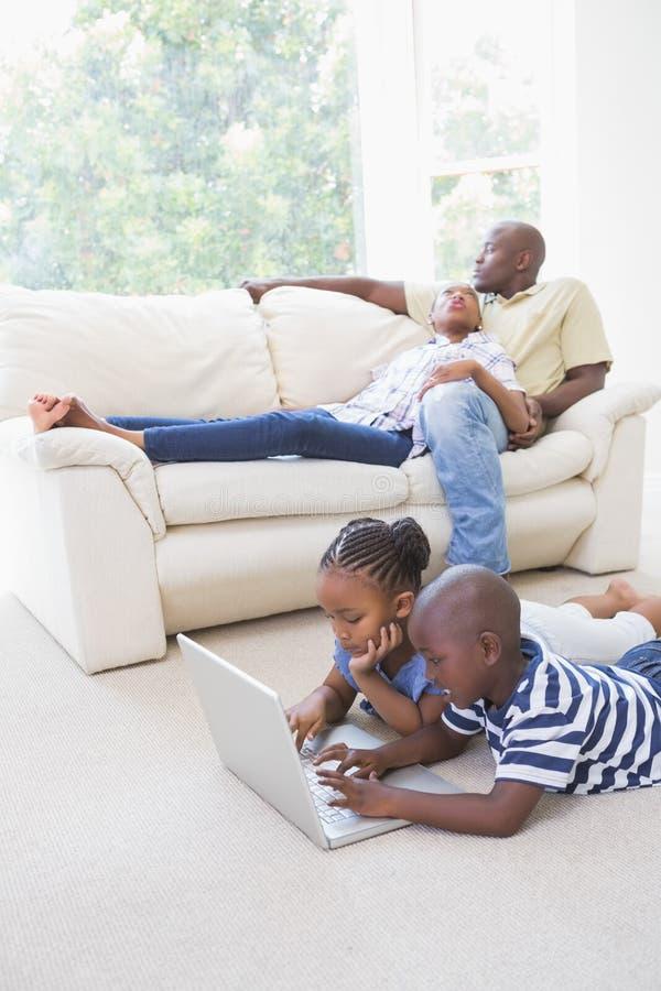 Download Enfants De Mêmes Parents Heureux à L'aide De Leur Ordinateur Portable Image stock - Image du contenu, intime: 56484577