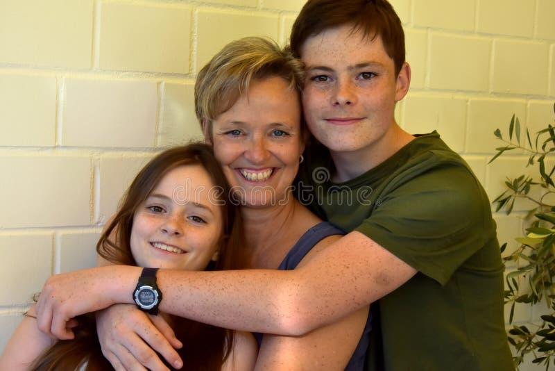 Enfants de mêmes parents heureux et leur mère image stock