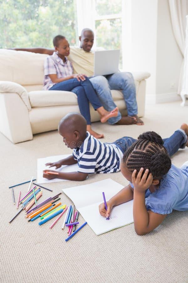 Download Enfants De Mêmes Parents Heureux Sur Le Dessin De Plancher Photo stock - Image du noir, contenu: 56483570