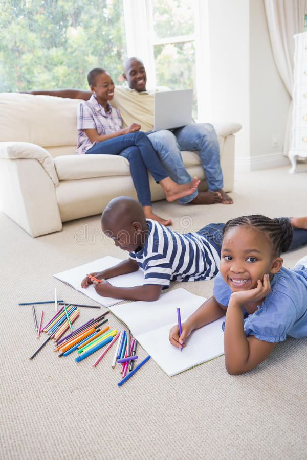 Download Enfants De Mêmes Parents Heureux Sur Le Dessin De Plancher Photo stock - Image du noir, occasionnel: 56484560