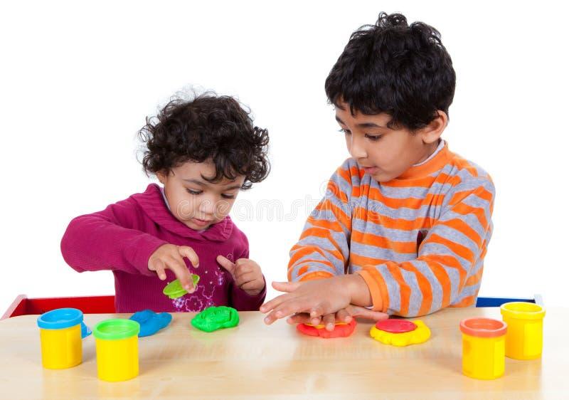 Enfants de mêmes parents jouant avec la pâte de pièce images libres de droits