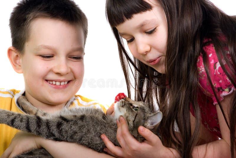 Enfants de mêmes parents jouant avec leur animal familier images stock
