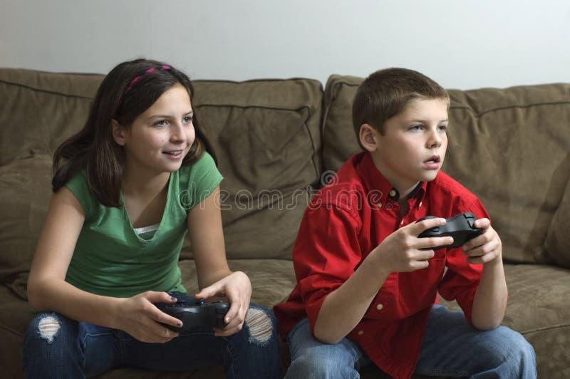 Enfants de mêmes parents jouant un jeu vidéo photo stock