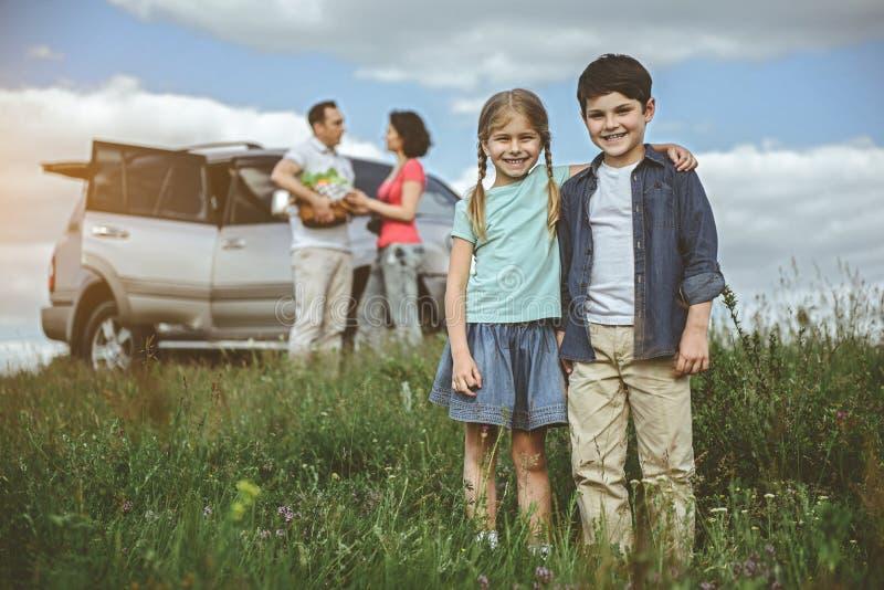 Enfants de mêmes parents joyeux ayant l'amusement dans la nature ensemble photographie stock