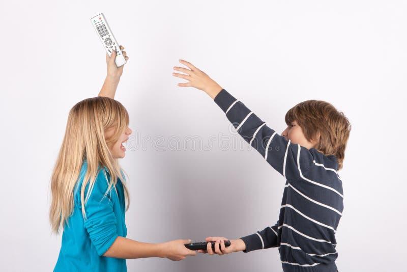Enfants de mêmes parents luttant pour des télécommandes de TV images stock
