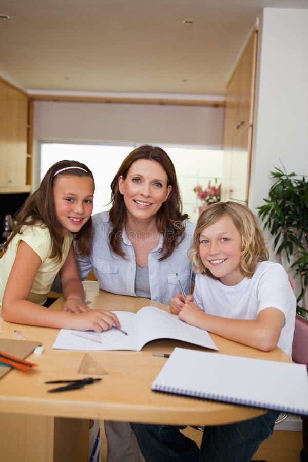 Enfants de mêmes parents obtenant l'aide avec des devoirs de la mère photos libres de droits