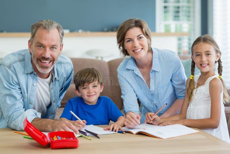 Enfants de mêmes parents obtenant l'aide avec des devoirs des parents photographie stock libre de droits