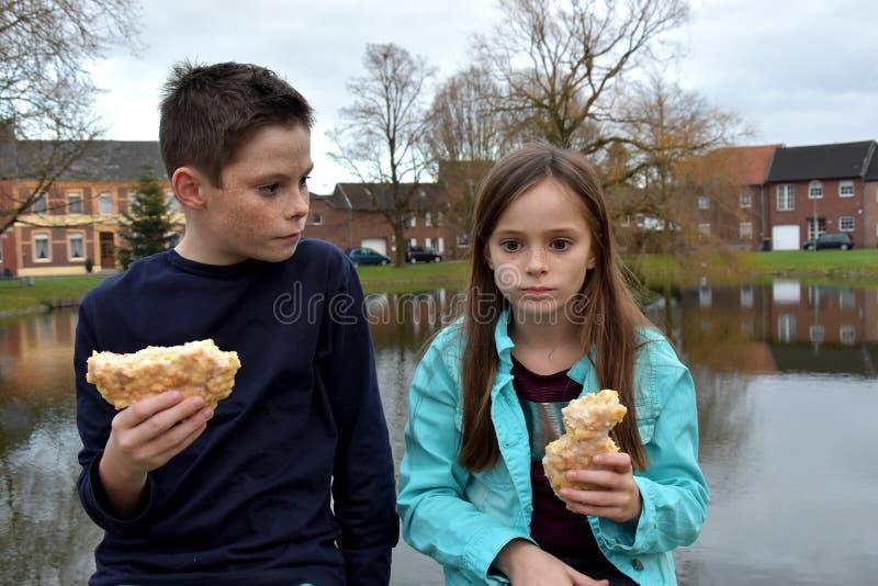 Enfants de mêmes parents partageant la pâtisserie photos stock
