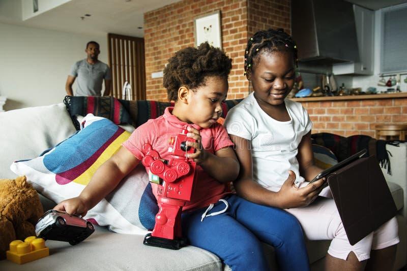 Enfants de mêmes parents passant le temps de qualité ensemble utilisant le comprimé image stock
