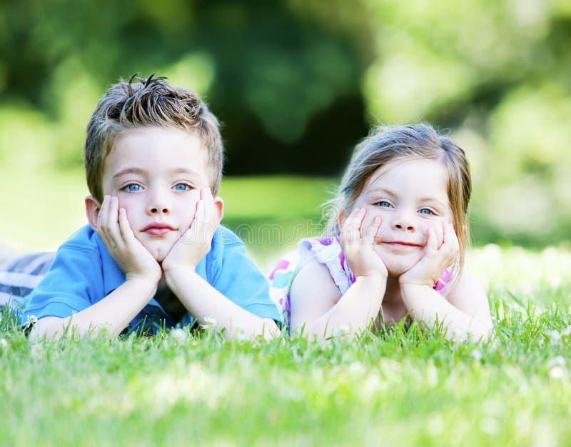 Enfants de mêmes parents s'étendant dans l'herbe images stock