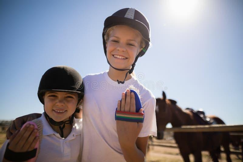 Enfants de mêmes parents se tenant ainsi que la brosse dans le ranch photographie stock