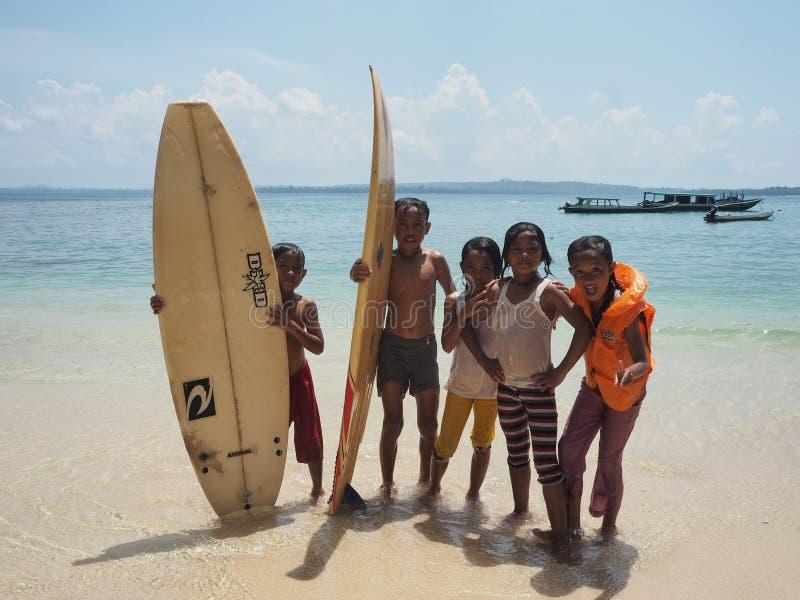 Enfants de Mnetawai jouant dans la plage avec des planches de surf photo libre de droits