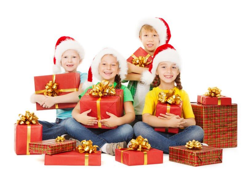 Enfants de Noël heureux tenant des présents Aides de Santa avec des cadeaux photo libre de droits