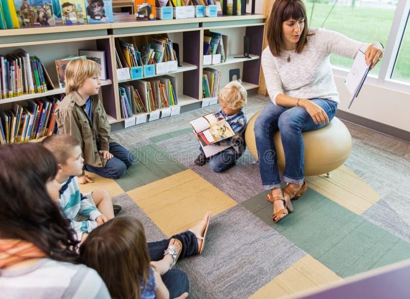 Enfants de Reading Book To de professeur dans la bibliothèque photos libres de droits