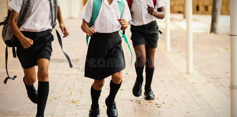 Enfants de sourire d'école fonctionnant dans le couloir photographie stock libre de droits