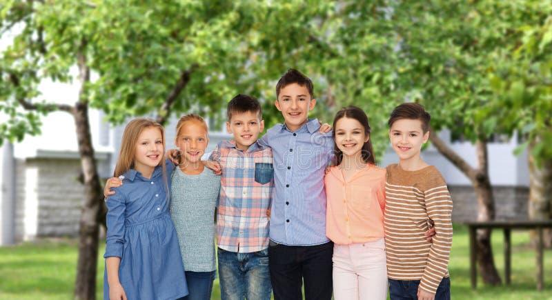Enfants de sourire heureux étreignant au-dessus de l'arrière-cour photo stock