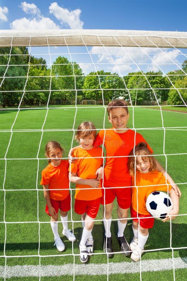 Enfants de sourire se tenant étroits avec le football photos libres de droits