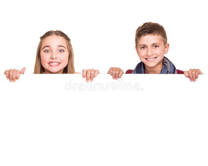 Enfants derrière un conseil blanc images libres de droits