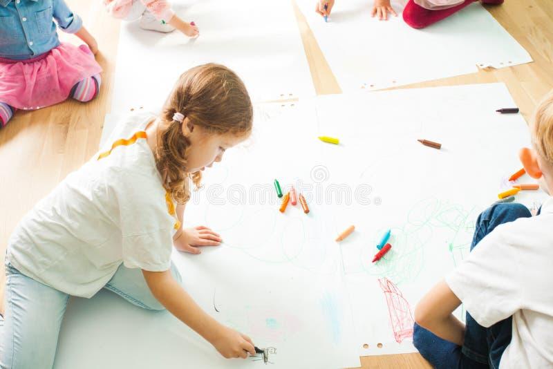 Enfants dessinant avec des crayons sur un plancher en bois photographie stock