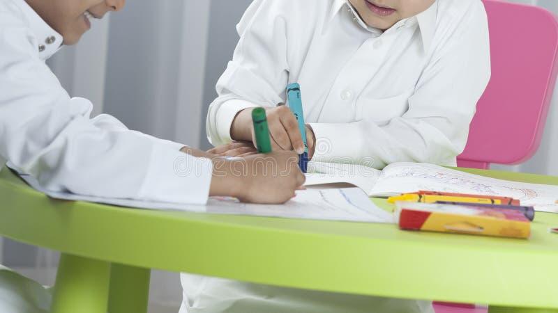 Enfants dessinant avec les crayons colorés à une table image stock