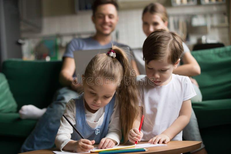 Enfants dessinant avec les crayons colorés tandis que parents à l'aide de l'ordinateur portable photo stock