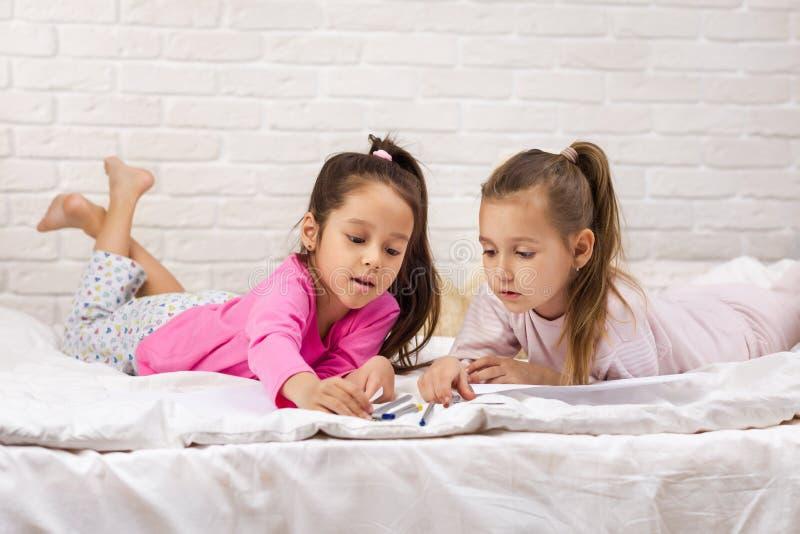 Enfants dessinant des images tout en se trouvant sur le lit images stock
