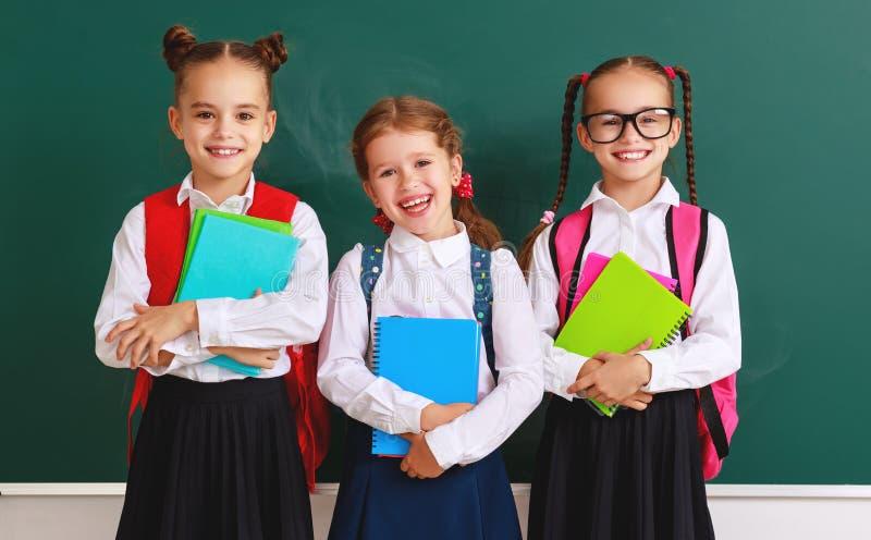 Enfants drôles de groupe écolier et écolière, garçon d'étudiant et fille au sujet de tableau noir d'école photographie stock libre de droits