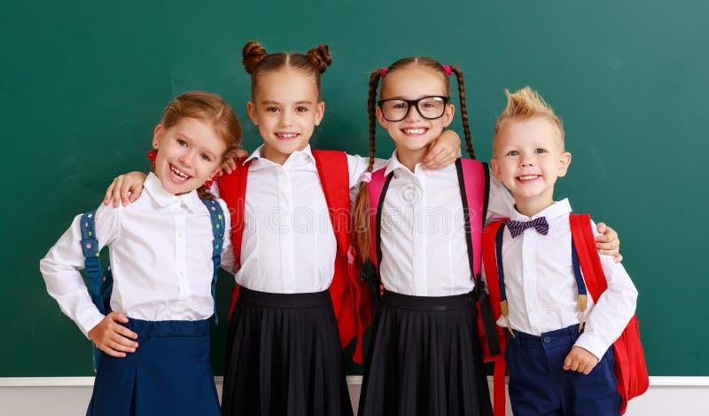 Enfants drôles de groupe écolier et écolière, garçon d'étudiant et fille au sujet de tableau noir d'école image stock