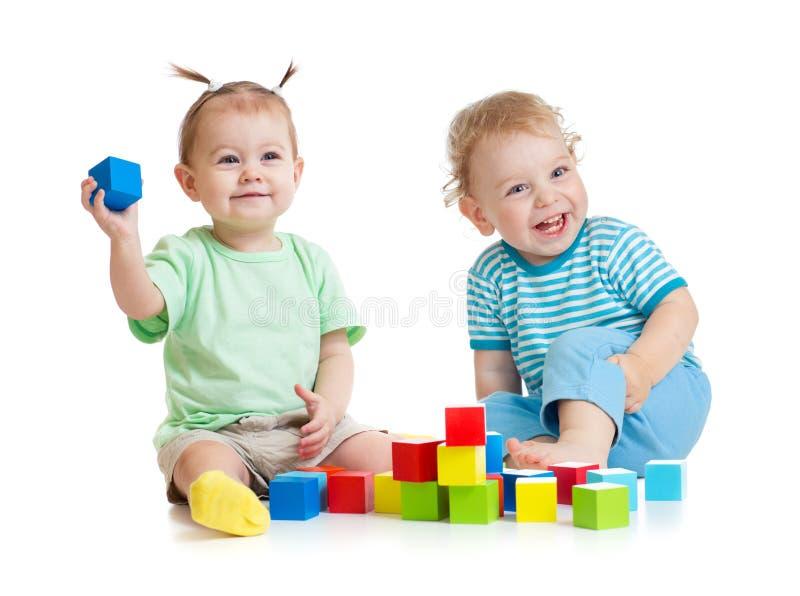 Enfants drôles jouant les jouets colorés d'isolement sur le blanc photos stock