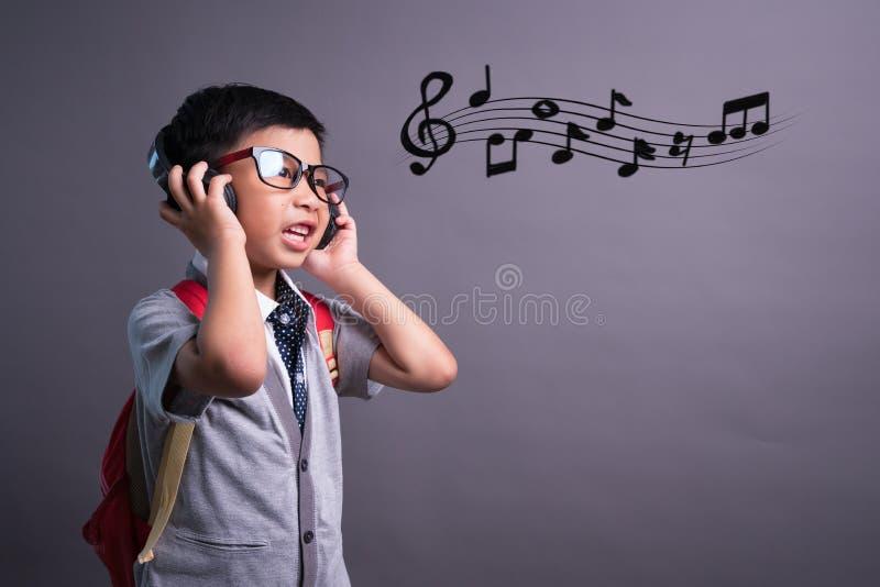 Enfants drôles mignons dans le studio de danse, petit garçon mignon dans des écouteurs écoutant la musique sur le fond de couleur photos libres de droits